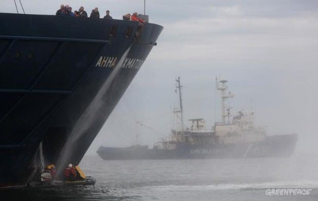 Activists are hosed with water by workers aboard the Anna Akhmatova.
