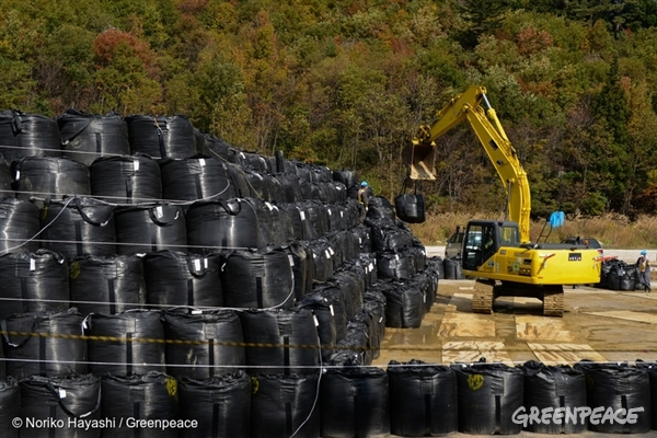 Piles of bags containing contaminated soil, mud and grass are covered and separated at a site in Iitate village.  Members of the Greenpeace radiation monitoring team check contamination levels in Watari and in Central Fukushima City, three and a half years after the nuclear accident.27 Oct, 2014 © Noriko Hayashi / Greenpeace