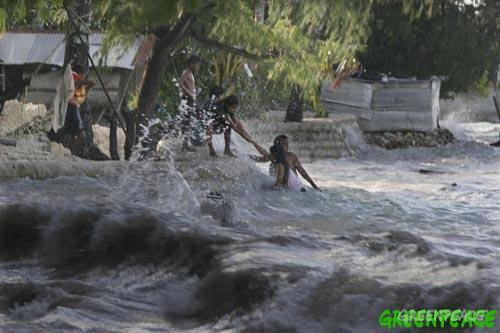 A family living next to the sea in the village of Betio, on the South Pacific island of Kiribati, pull themselves from the high waves of the 'king tide'