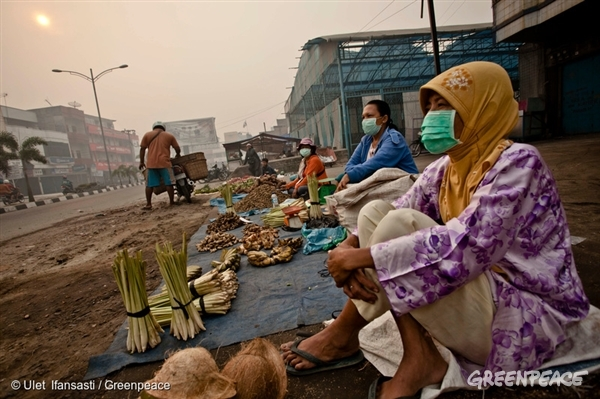 Market vendors in Dumai wear masks to protect themselves from air pollution caused by the forest fires in Sumatra. 23 Jun, 2013