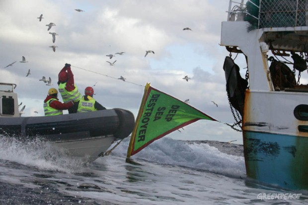 Greenpeace activists hang a banner on the trawl doors of the EU deep seabottom trawler Playa de Menduina, to protest against the destruction causedby this fishing practice.
