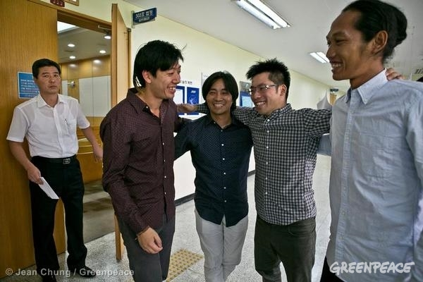Gwangan Bridge Activists Court Case in South Korea. Greenpeace activists, from second from left, Van Pham (USA), Jun Kwon Song (South Korea), Chun-Ta Lee (Taiwan), and Adhonal Canarisla (Indonesia) embrace outside the courtroom at Busan District Court. Greenpeace commended South Korea's judicial system for upholding people's right to peaceful protest after it ruled that the four Greenpeace activists who demonstrated on Busan's Gwangan (also known as Gwangandaegyo) bridge last 9th July to raise awareness about South Korea's inadequate nuclear emergency plans, were justified to perform such action due to real threats by nuclear energy on citizens of Busan. 08/22/2013 © Jean Chung / Greenpeace
