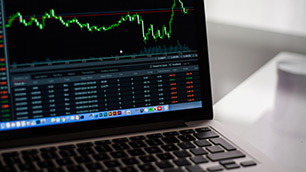 Laptop showing stock market chart.