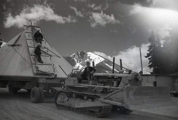 Photo depicting the observatory dome as it is transported to the observatory site at Climax, including workers involved in the transport. Roberts established the High Altitude Observatory at Climax in 1940. The Climax Molybdenum Company supported the construction of the observatory. Walter Raymond Allen, an employee at Climax Molybdenum Company, took this photograph.